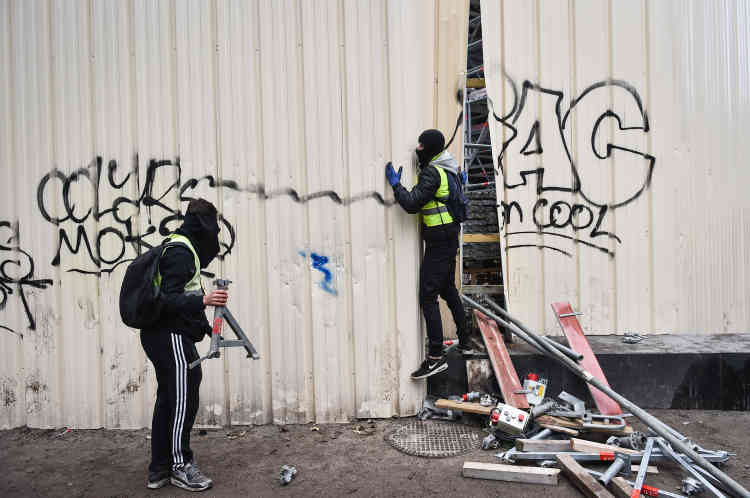 A Bordeaux, en marge, des manifestants ouvrent une brèche dans une palissade de chantier afin d'y récupérer des projectiles et du matériel pour confectionner des barricades.
