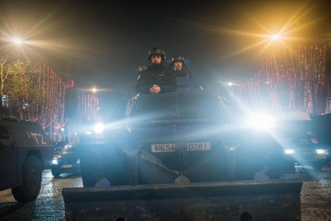 Paris, le 8 décembre 2018. Des «gilets jaunes» rassemblés sur l'avenue des Champs Elysées se retrouvent nassés par les forces de l'ordre. Un véhicule blindé de la Gendarmerie Nationale aide à la manoeuvre en vue de l'évacuation de l'avenue en fin de journée.
