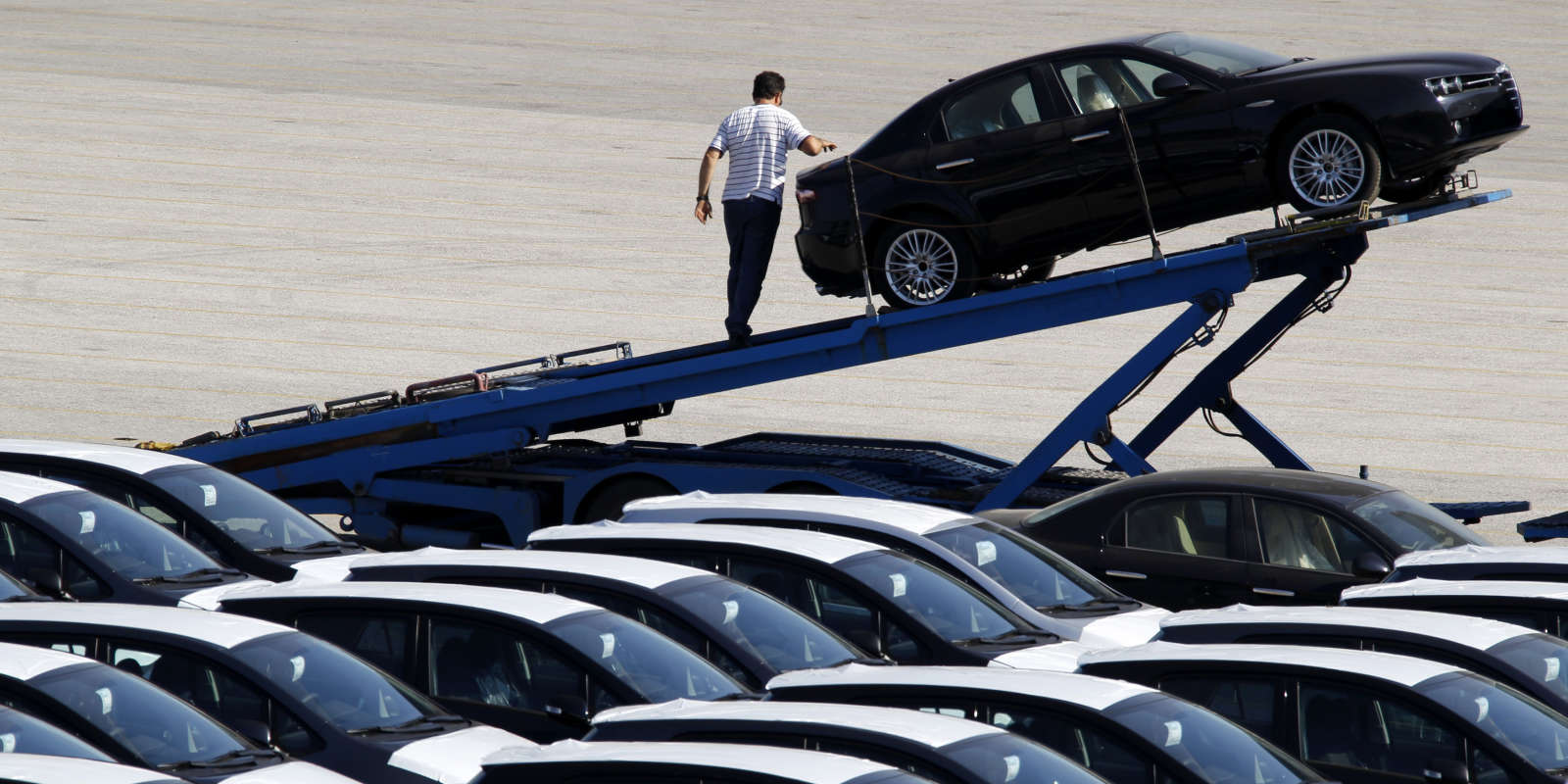A man prepares to unload a car from a truck at a cargo terminal at Piraeus port near Athens July 8, 2011. Newly-issued car licenses in Greece dropped 42 percent during the first half of 2011 compared to the same period in 2010, according to the Greek Statistics Authority. REUTERS/Yiorgos Karahalis (GREECE - Tags: TRANSPORT POLITICS BUSINESS) - GM1E7781FQ001