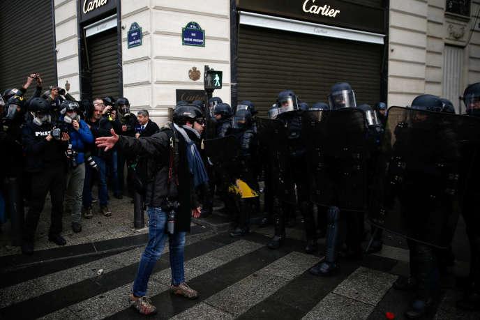 Un photographe face à des policiers lors de la manifestation des « gilets jaunes» à Paris, le 8décembre.