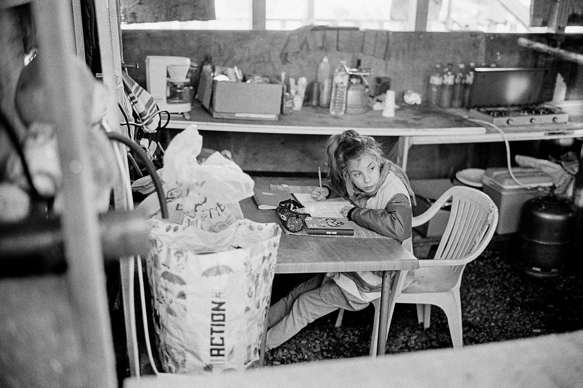 Rond-point appelé de «la Zatar», lundi10décembre.Une petite fille fait ses devoirs sous la surveillance de ses parents.