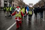 "A protester dressed as Santa Claus wears a yellow vest (gilet jaune) during a demonstration against rising costs of living they blame on high taxes on the Champs-Elysees avenue near the Arc de Triomphe in Paris, on December 15, 2018. The ""Yellow Vests"" (Gilets Jaunes) movement in France originally started as a protest about planned fuel hikes but has morphed into a mass protest against President's policies and top-down style of governing. / AFP / Abdul ABEISSA"