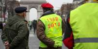 """Protesters wearing yellow vests (gilets jaunes) part in a demonstration on the Champs Elysees Avenue by the Arc de Triomphe in Paris, on December 15, 2018, to protest against rising costs of living they blame on high taxes. The """"Yellow Vests"""" (Gilets Jaunes) movement in France originally started as a protest about planned fuel hikes but has morphed into a mass protest against President's policies and top-down style of governing. / AFP / Zakaria ABDELKAFI"""