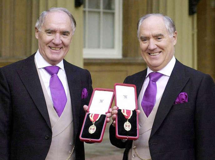 Tout juste anoblis par la reine, les frères jumeaux Barclay montrent avec fierté leur insigne de chevalier, dans la cour du palais de Buckingham. Cette photo, qui date de 2000, est l'une des rares que l'on possède de Sir David et Sir Frederick.