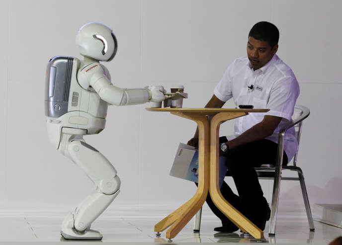 Un robot construit par Honda sert un thé à un visiteur dans un salon à Johannesbourg, en octobre 2011.