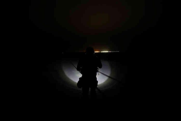 Un policier, à la lueur d'une lampe torche, suit lui aussi une ligne de chemin de fer, à Arica, le 14novembre.