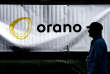 "An Orano employee passes by an sign reading ""Orano"" at the new conversion site ""Philippe Coste COMURHEX II Uranium"" located on the Tricastin nuclear plant site, in Pierrelatte on September 10, 2018. - Orano (formerly Areva) inaugurated on September 10, 2018 at Tricastin (Drôme) its new uranium conversion plant Comurhex II, with a delay of six years and a bill of more than one billion euros, doubled compared to the first estimate. (Photo by JEFF PACHOUD / AFP)"