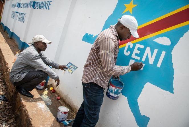 Des ouvriers peignent le logo de la Commission électorale nationale indépendante (CENI) de la République démocratique du Congo à Lubumbashi, le 20 décembre 2018.