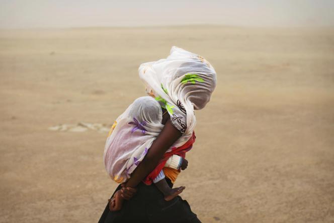 Une femme porte son bébé lors d'une tempête de sable à Tombouctou, en juillet 2013.