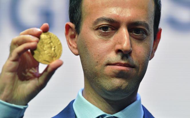 La mathématicien Caucher Birkar montre la nouvelle médaille Fields qui lui a été donnée le 8 août, après que celle qui lui avait été attribuée une semaine plus tôt lui ait été volée quelque minutes après la remise du prix, à Rio de Janeiro.