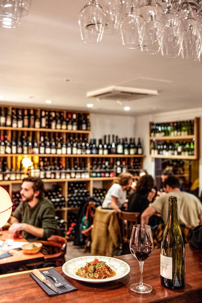 Un bar à vins avec son mobilier de bois clair, ses murs dépouillés et ses étagères garnies de bouteilles.