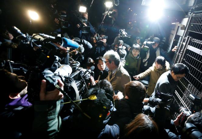 Encerclé par les journalises, l'avocat de Carlos Ghosn tente de quitter le centre de détention de Tokyo, le 20 décembre.