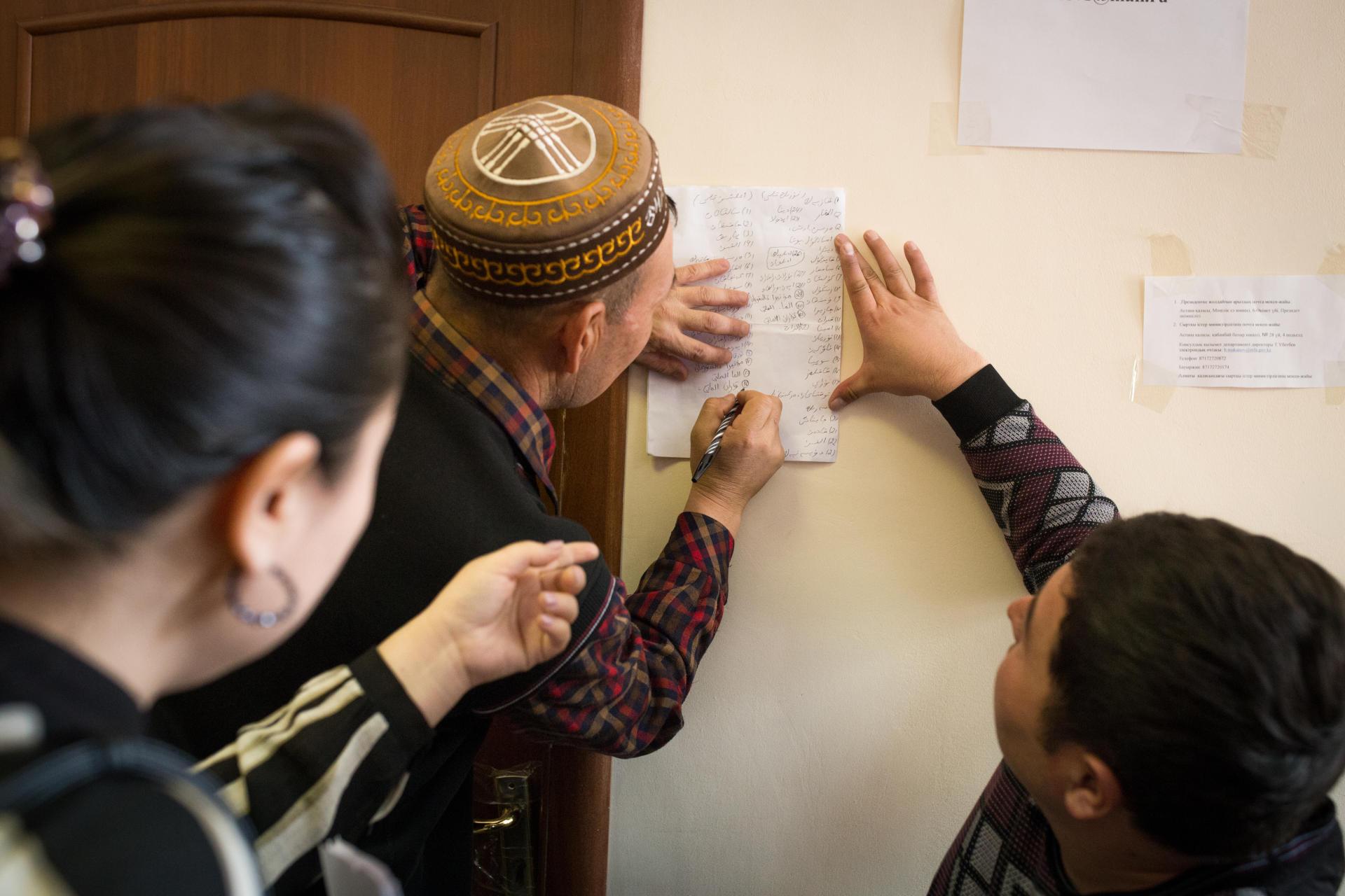 Des bénévoles aident chacun à écrire des lettres à Michelle Bachelet, la Haut-Commissaire des Nations unies aux droits de l'homme et au président kazakh, Noursoultan Nazarbaïev, pour les interpeller sur leurs «disparus». Des familles brandissent le portait de leurs proches détenus ou retenus dans la Xinjiang chinois. A Almaty, au Kazakhstan, en décembre 2018.