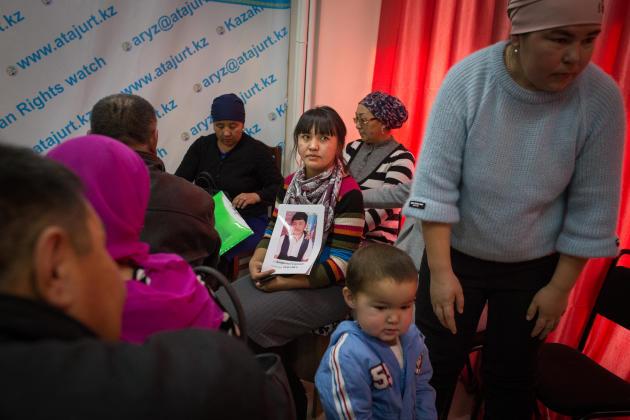 Dans les locaux de l'association Atazhurt, une femme tient le portrait d'un de ses proches disparu en Chine. A Almaty, au Kazakhstan, en décembre 2018.