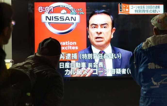 Des passants devant un écran de télévision montrant la photo de Carlos Ghosn, le 21 décembre à Tokyo, au Japon.