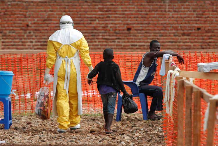 Un enfant probablement contaminé par Ebola est escorté par un travailleur sanitaire dans un centre de transit à Beni, dans la province du Nord-Kivu, en République démocratique du Congo, le 15 décembre.