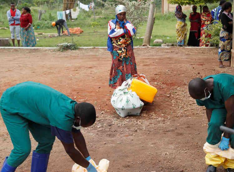 Une femme regarde le personnel sanitaire enlever leurs tenues de protection après avoir porté le cercueil d'un bébé dont la mort a probablement été causée par Ebola. ABeni, dans la province du Nord-Kivu, en République démocratique du Congo, le 18 décembre.