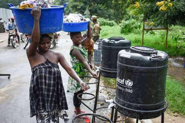 Des gens venant de RDC se lavent les mains à un point de contrôle sanitaire à la frontière entre l'Ouganda et la RDC, à Mpondwe, dans l'ouest de l'Ouganda, le 12 décembre.