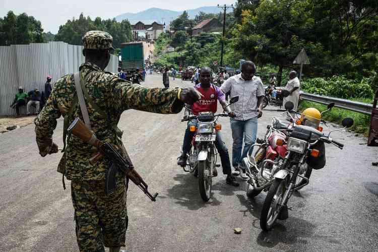 Un militaire ougandais demande à la population venant de RDC de passer un contrôle sanitaire à la frontière entre l'Ouganda et la RDC, à Mpondwe, dans l'ouest de l'Ouganda, le 12 décembre.