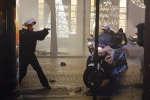 Un policier sort son arme face aux manifestants, le samedi 22 décembre aux Champs-Elysées, à Paris.