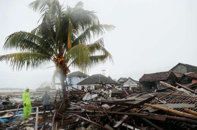 Des hommes parmi des débris et des biens endommagés sur la plage après le tsunami, à Sumur, province de Banten, en Indonésie, le 26 décembre 2018.