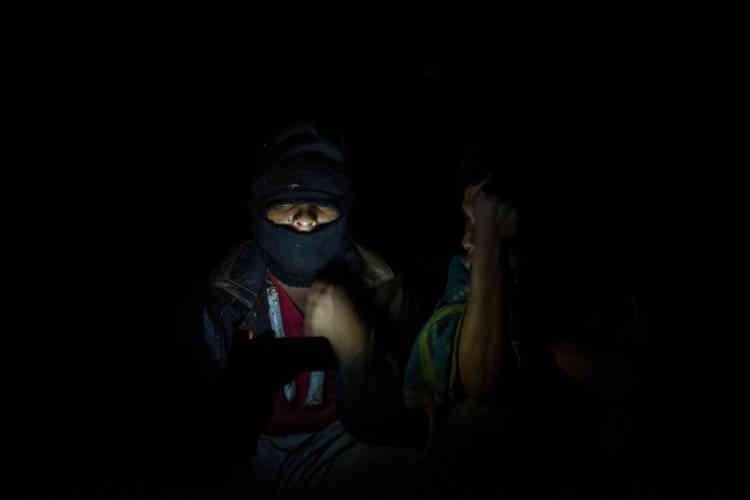 Les attaques des fermiers se produisent principalement pendant la nuit et pour cette raison, les indigènes se relaient à la position de sentinelle nocturne. Ici, deux jeunes de l'ethnie kaiowá regardent une vidéo de la chanteuse brésilienne Anitta sur leur téléphone.
