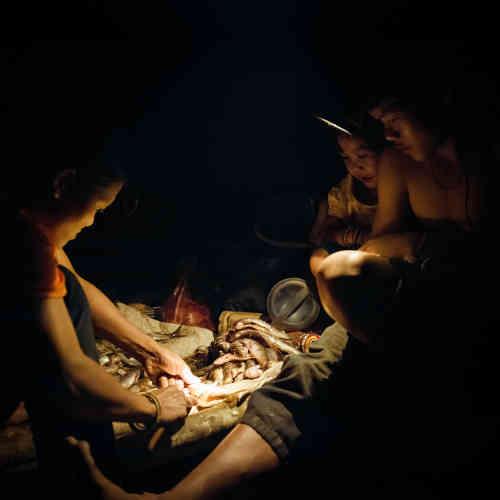 Préparation du poisson fraîchement pêché. Il n'y a pas d'éléctricité, la famille n'utilise que des lampes frontales à piles ou solaires pour s'éclairer une fois la nuit tombée.