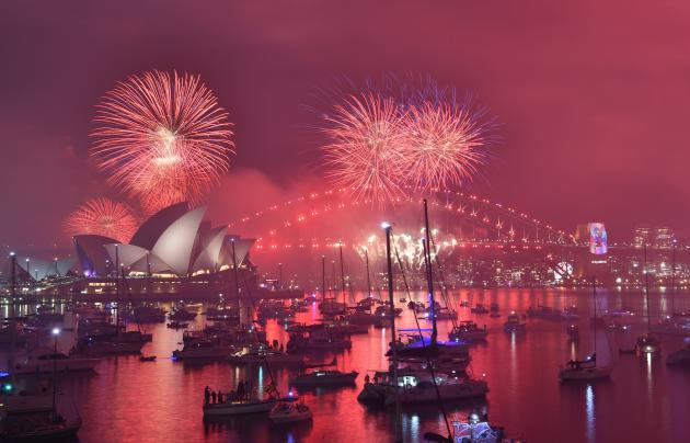 Les feux d'artifice destinés aux familles illuminent le port et l'opéra de Sydney, en Australie, avant le passage à la nouvelle année, le 31 décembre.