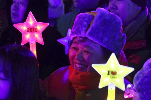 Les habitants de Pékin observent le décompte des minutes avant minuit, le 31 décembre.