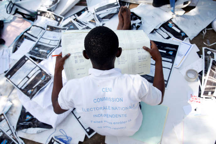 Un membre de la Commission électorale nationale indépendante examine un bulletin de vote dans un centre de Kinshasa le 1er janvier.