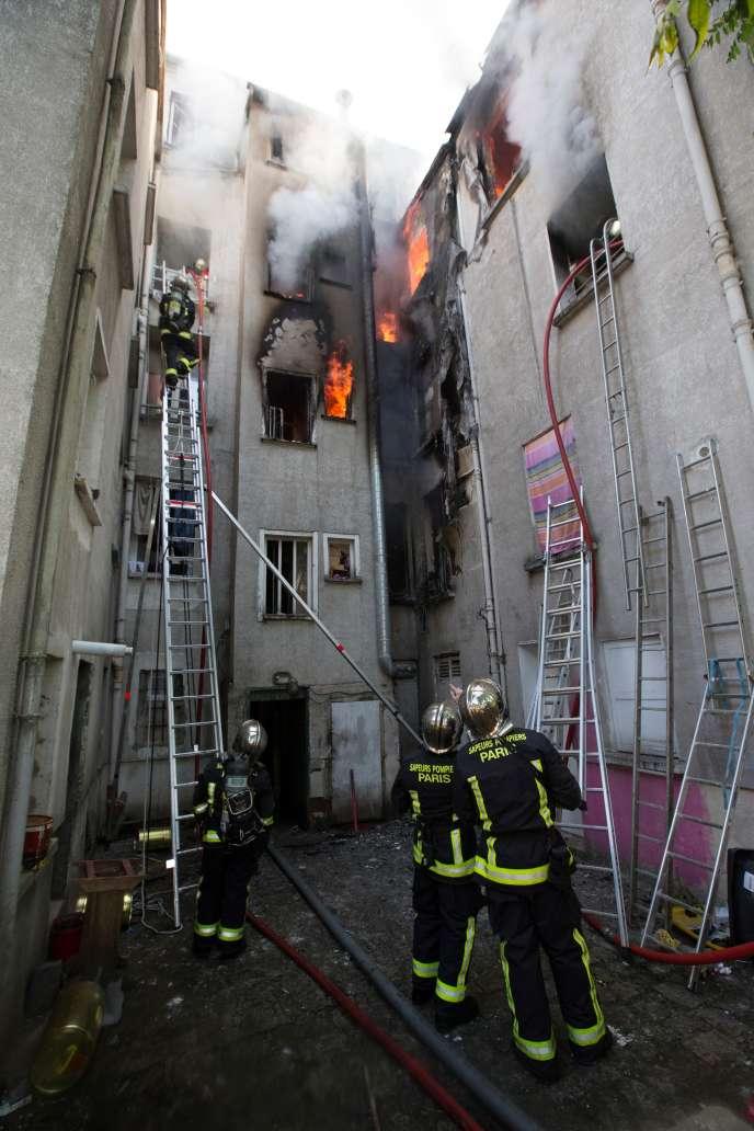 Des pompiers tentent d'éteindre un incendie qui a pris feu dans un immeuble ducentre de Saint-Denis (Seine-Saint-Denis), le 6 juin 2016.