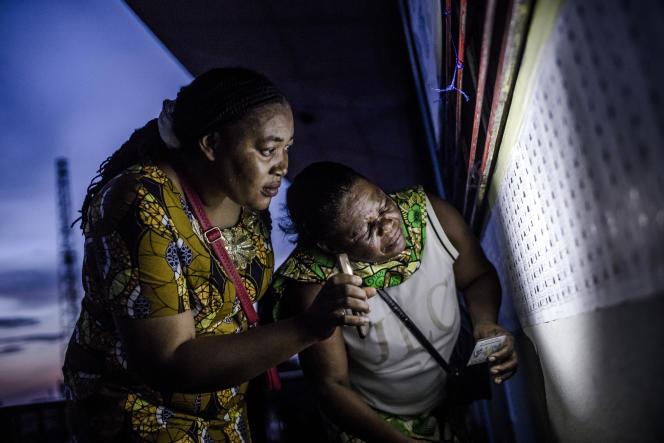 Des habitantes de Kinshasa examinent une liste électorale à la lumière d'un smartphone, le 30décembre 2018.