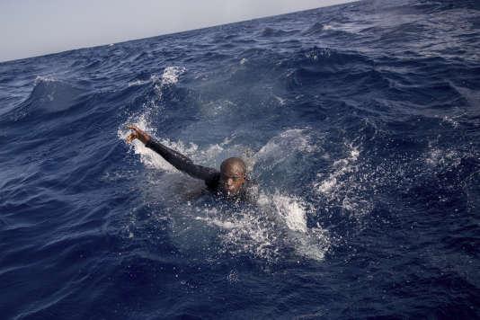 Un migrant tente de monter à bord d'un canot de l'ONG allemande Sea-Watch, au large de la Libye, le 6 novembre 2017.