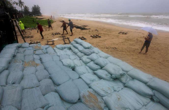 Des Thaïlandais placent des sacs de sable afin de protéger les propriétés en bord de mer à Songkhla, à l'approche de la tempête Pabuk, jeudi 3 janvier.