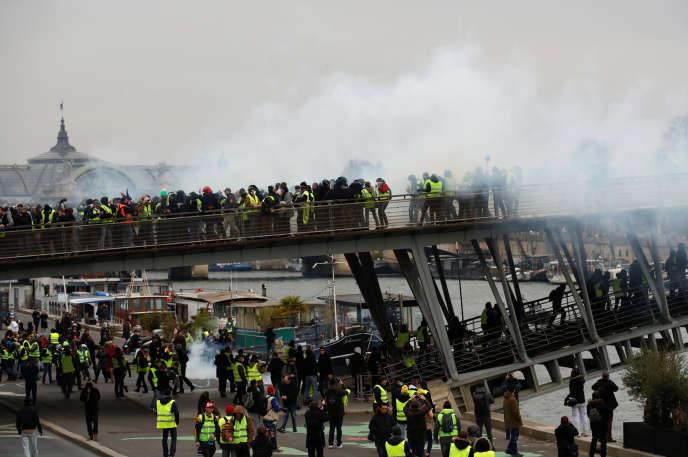 Des« gilets jaunes» sont repoussés par des gaz lacrymogènes lancés par les forces de l'ordre, samedi 5 janvier à Paris.