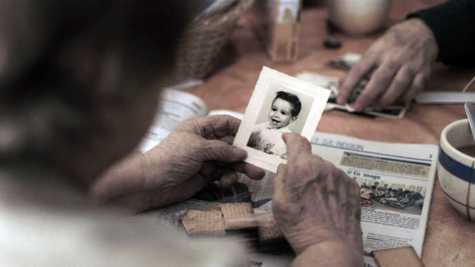 Capture d'écran du film projeté pendant le spectacle « Retour à Reims » où la mère de Didier Eribon montre une photo de lui enfant.