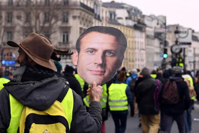 Un « gilet jaune» défile avec un portrait d'Emmanuel Macron sur le quai Saint-Michel, à Paris, le 5 janvier.