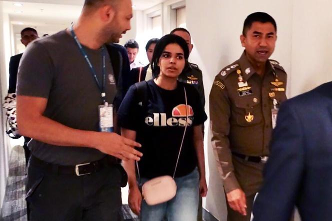RahafMohammed Al-Qanunescortée vers la sortie de l'aéroport de Bangkok, le 7 janvier.