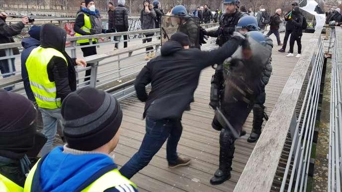 Christophe Dettinger (de dos), boxant un policier sur la passerelle Sédar-Senghor, à Paris, le 5 janvier.