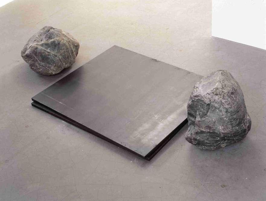 """«Parmi les œuvres les plus iconiques de Lee Ufan, figurent les sculptures qui mettent en situation des plaques de métal et des pierres. """"J'ai fini par choisir la pierre comme représentant du """"non-faire"""", dit l'artiste. La pierre possède en elle un temps aussi long que celui de la Terre. Ce fragment du temps incalculable est un élément qui peut être analysé par le biais des sciences mais qui reste une entité incompréhensible. C'est un objet réel mais qui dépasse l'objet lui-même."""" L'œuvre existe lorsque la pierre choisie rencontre l'acier, en plaques nettes ou en barres usinées, que Lee Ufan définit comme """"des produits de la société industrielle [qui] reconstituent, en peu de temps, sous une forme abstraite, les composants extraits d'un minerai naturel.""""»"""