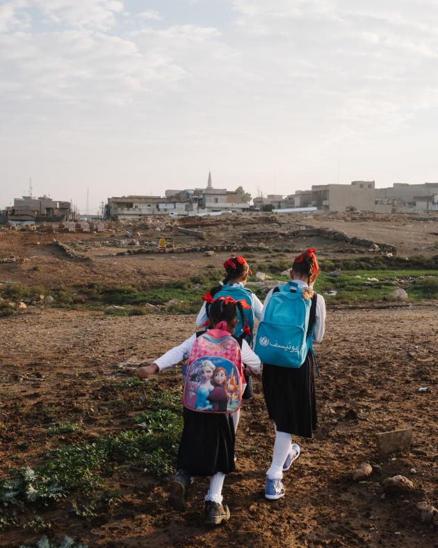 Des petites filles traversent le cimetière pour se rendre à l'école.ALEXANDRA ROSE HOWLAND POUR LE MONDE