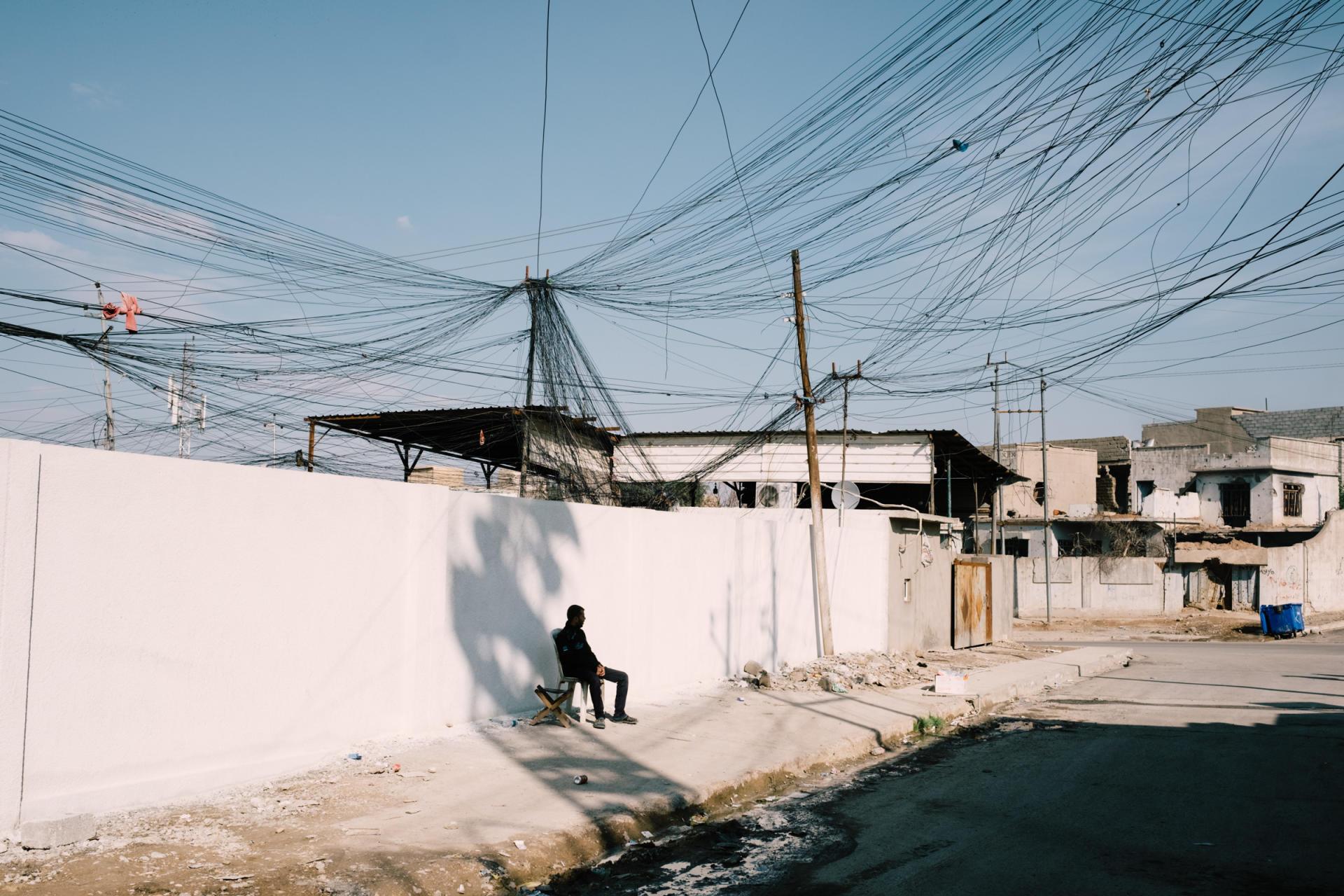 Un commerçant assis sous les câbles qui alimentent en électricité la vielle ville.ALEXANDRA ROSE HOWLAND POUR LE MONDE
