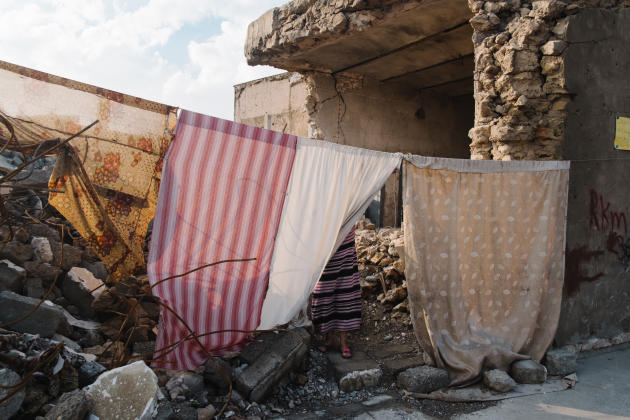 Yunis et sa famille sont revenus vivre dans leur maison endommagée pendant la guerre. Des draps séparent la maison de la rue.ALEXANDRA ROSE HOWLAND POUR LE MONDE