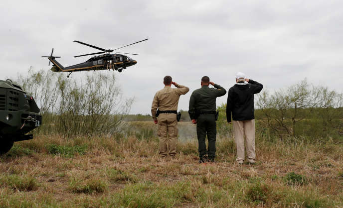 Donald Trump (à droite) salue un hélicoptère patrouillant au-dessus du Rio Grande, le 10 janvier, au Texas (Etats-Unis).