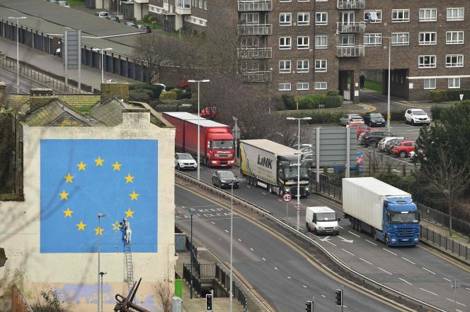 Des camions roulent près d'une peinture murale de l'artiste Banksy lors d'un test de décongestion du trafic dans l'hypothèse d'un Brexit sans accord avec l'UE, à Douvres, le 7 janvier. Le tiers du commerce britannique passe par le port de Douvres. En cas de Brexit sans accord, chaos et embouteillages monstres sont annoncés.
