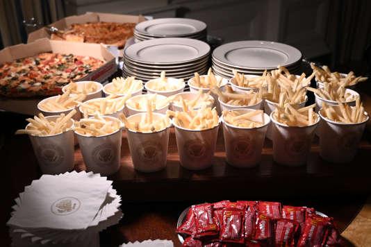 Des pizzas et des frites dans des gobelets portant le sceau du président des Etats-Unis.