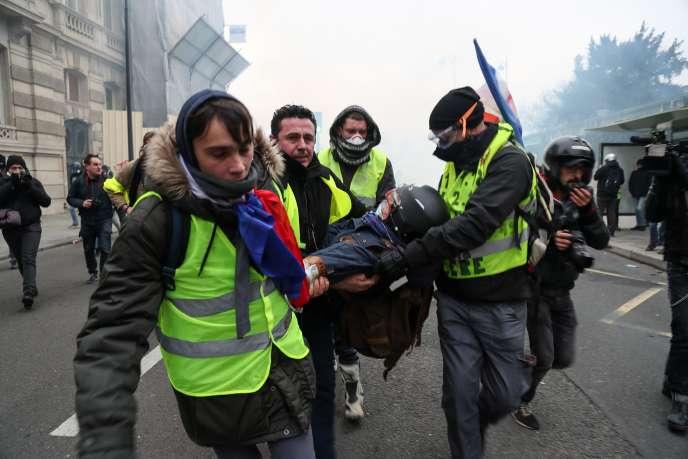 Des «gilets jaunes» viennent en aide à un photographe, blessé lors d'une manifestation à Paris, le 5 janvier.