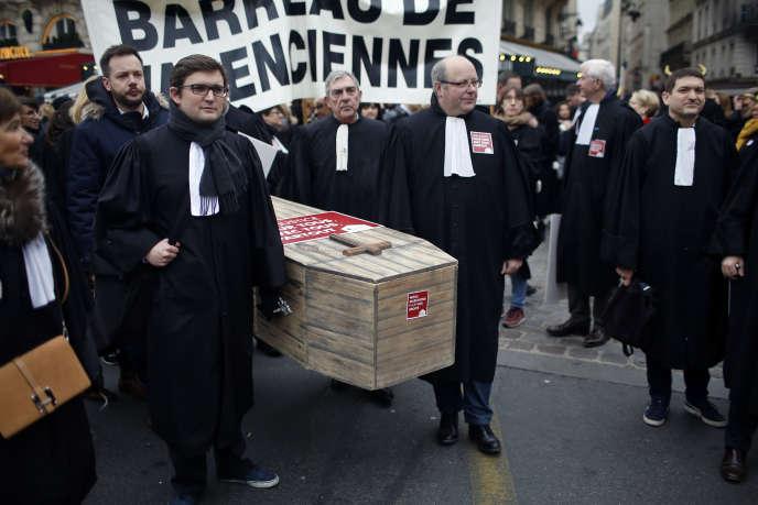 Des avocats tiennent un cercueil alors qu'ils manifestent contre un projet de loi du gouvernement sur la justice, à Paris, le mardi 15 janvier 2019.
