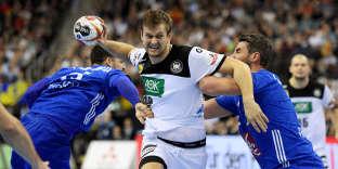 Le joueur allemand Fabian Bohm face aux Français Mathieu Grebille et Luka Karabatic, à Berlin, le 15 janvier.