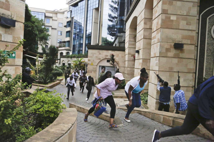 Des Kényans fuient sous les tirs des forces de sécurité et des terroristes qui ont attaqué un complexe hôtelier, à Nairobi, le 15 janvier.
